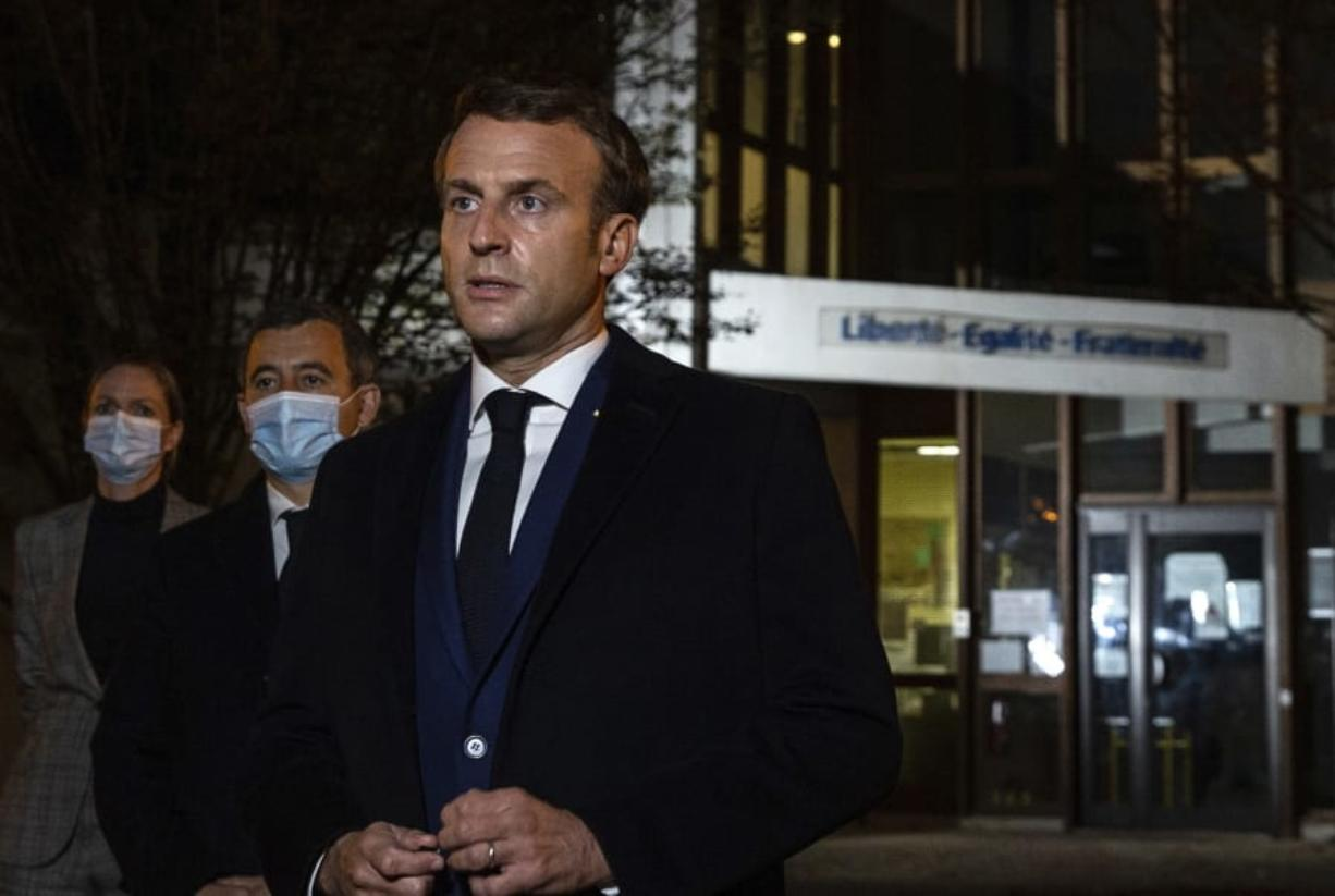 """French President Emmanuel Macron, flanked by French Interior Minister Gerald Darmanin, second left, speaks in front of a high school Friday Oct.16, 2020 in Conflans Sainte-Honorine, northwest of Paris, after a history teacher who opened a discussion with high school students on caricatures of Islam's Prophet Muhammad was beheaded. French President Emmanuel Macron denounced what he called an """"Islamist terrorist attack"""" against a history teacher decapitated in a Paris suburb Friday, urging the nation to stand united against extremism."""
