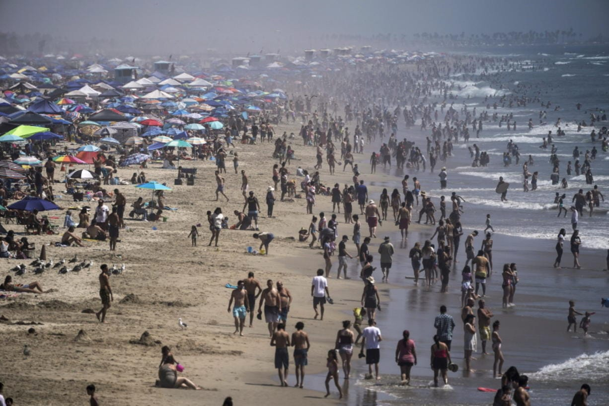 FILE - In this Saturday, Sept. 5, 2020 file photo, people crowd the beach in Huntington Beach, Calif., as the state swelters under a heat wave. On Wednesday, Oct. 14, 2020, the U.S. National Oceanic and Atmospheric Administration said the Earth reached a record hot September, saying that there's nearly a two-to-one chance that 2020 will end up as the globe's hottest year on record. (AP Photo/Jae C.