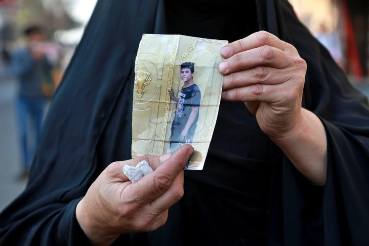 A woman holds a picture of her a missing son during anti-government protest in Baghdad, Iraq, Sunday, Feb. 23, 2020. There are 25 activists still missing since the protests erupted on Oct. 1, 2019, according to the semi-official Iraqi High Commission for Human Rights. No group has claimed responsibility but activists have blamed the militias.