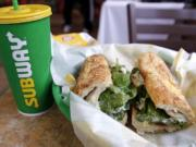 FILE - In this Friday, Feb. 23, 2018 file photo, the Subway logo is seen on a soft drink cup next to a sandwich at a restaurant in Londonderry, N.H.. Ireland's Supreme Court has ruled that bread sold by the fast food chain Subway contains so much sugar that it cannot be legally defined as bread.