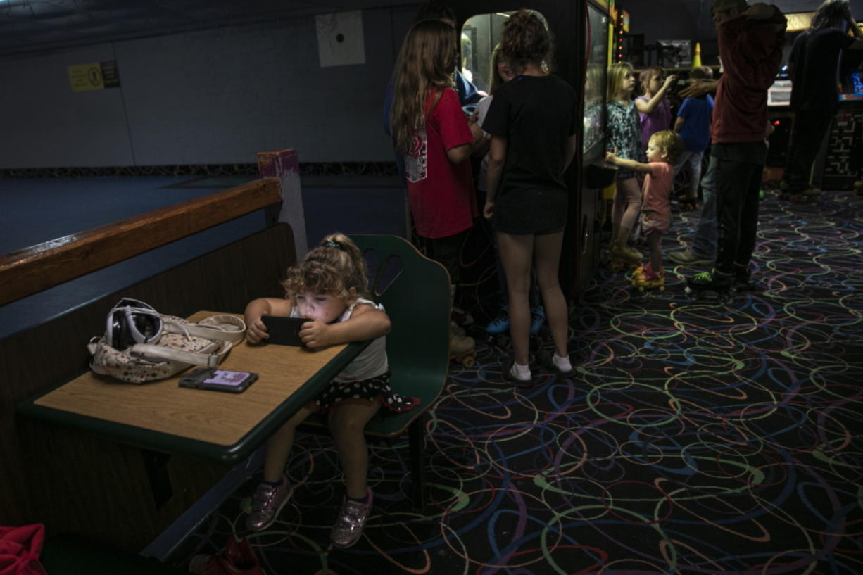 A girl is immersed in a smartphone game while others play in an arcade at a skating rink, Saturday, Aug. 1, 2020, in Anna, Ill.