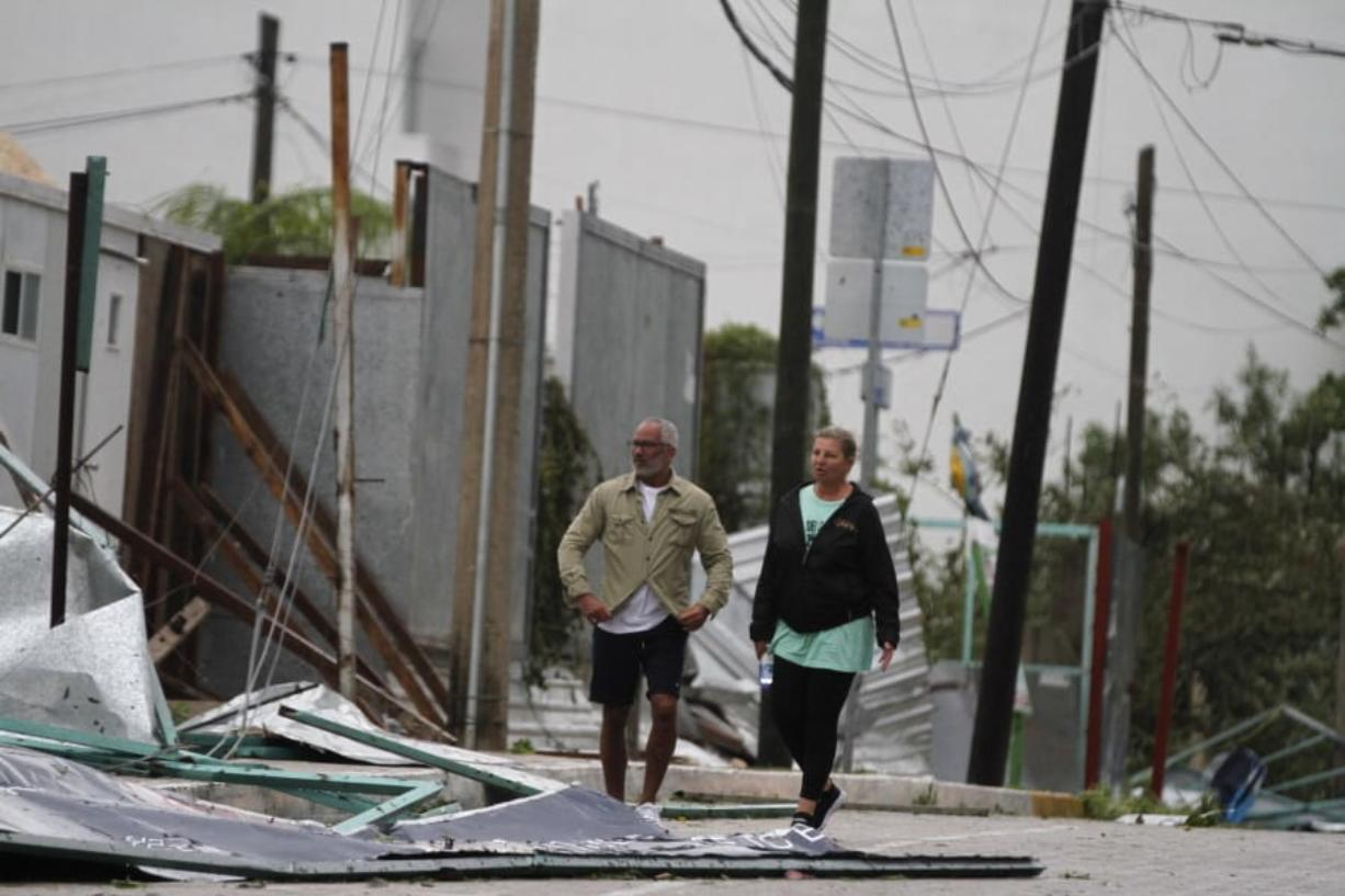 Tourists walk past debris littering the street after Hurricane Zeta's landfall in Playa del Carmen, Mexico, early Tuesday, Oct. 27, 2020. Zeta is leaving Mexico's Yucatan Peninsula on a path that could hit New Orleans Wednesday night.