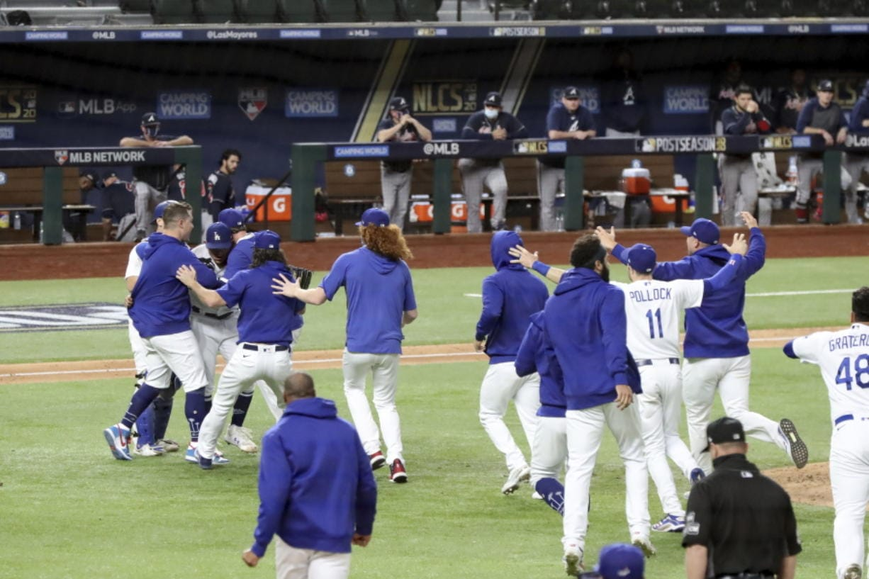 Los Angeles Dodgers players mob pitcher Julio Urias after they defeated the Atlanta Braves 4-3 in Game 7 of the National League Championship Series, Sunday in Arlington, Texas.