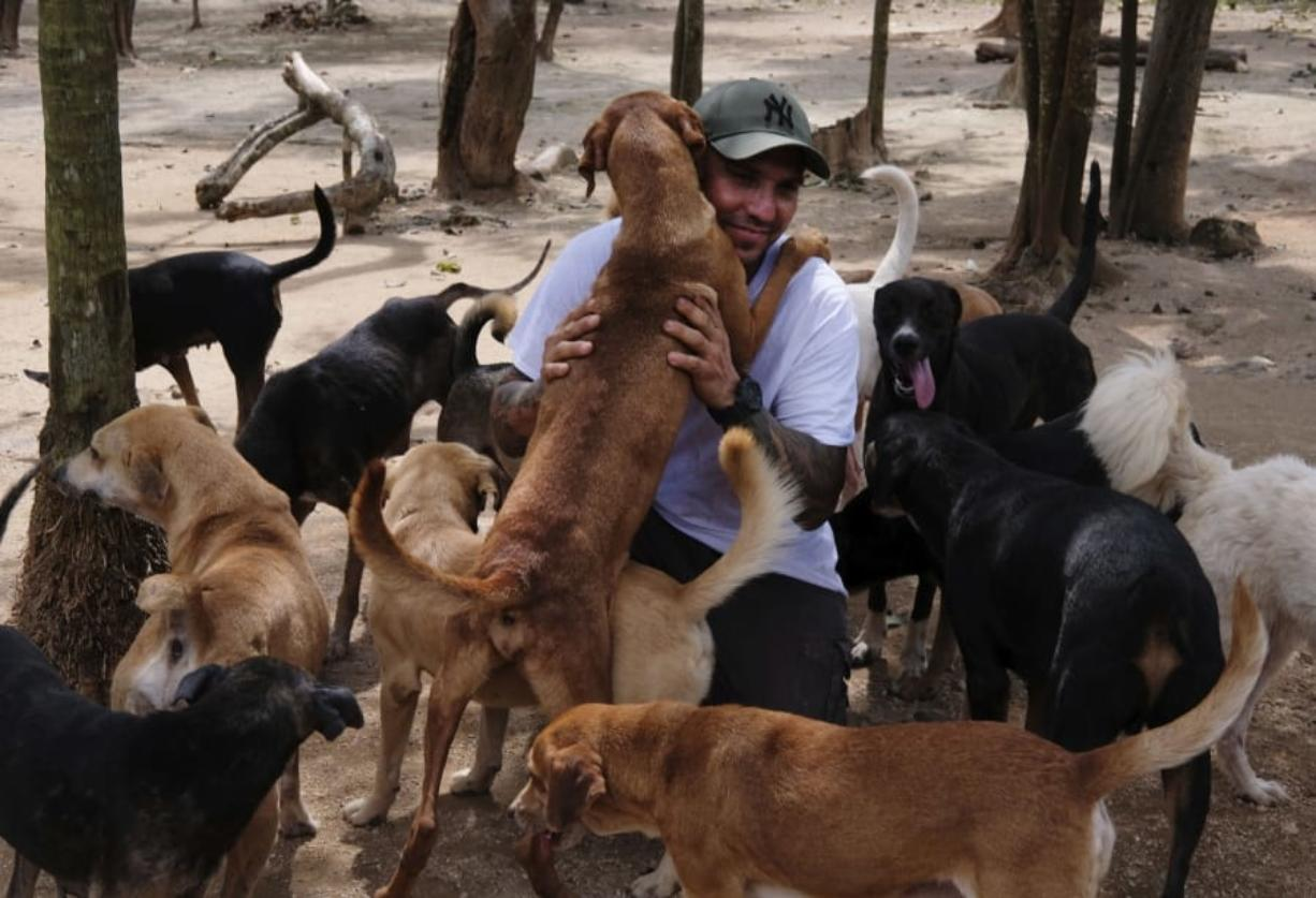 In this Oct. 13, 2020, photo, Ricardo Pimentel is greeted by dogs that he rescued at his Tierra de Animales (Land of Animals) shelter in Leona Vicario, Mexico. Pimentel sheltered about 300 dogs at his home during Hurricane Delta, and his story, which has gone viral, led people across the world to donate to the shelter.