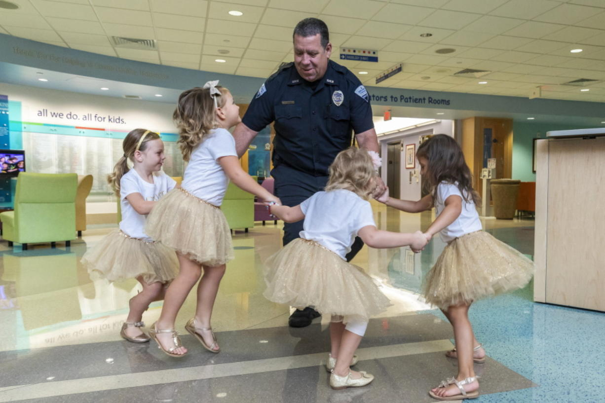 In this photo provided by Johns Hopkins All Children's Hospital, security guard David Dean dances with McKinley Moore, Avalynn Luciano, Lauren Glynn and Chloe Grimes at the hospital in St. Petersburg, Fla., Aug. 9, 2018. The girls, who were diagnosed with cancer in 2016 and became fast friends while undergoing treatment, reunite every year.