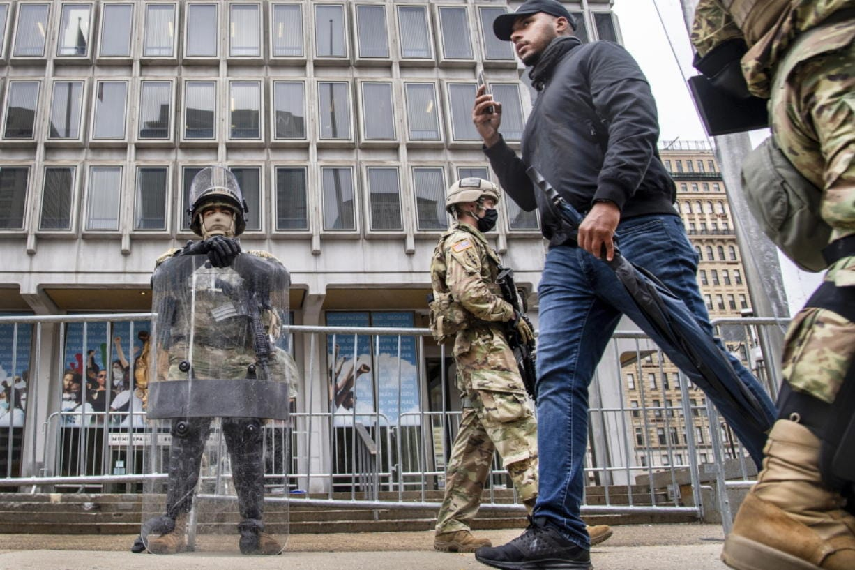 An unidentified pedestrian walks between members of the National Guard as they stand guard in front of the Philadelphia Municipal Services Building in Philadelphia, Pa., Friday, Oct. 30, 2020. (Jose F.