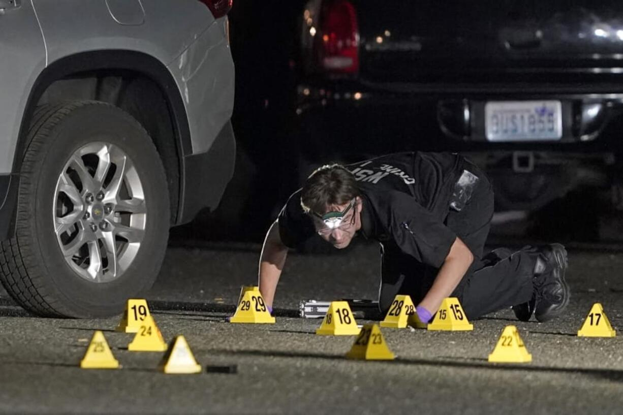 A Washington State Patrol Crime Lab worker looks at evidence markers in the early morning hours of Sept. 4 in Lacey, at the scene where Michael Reinoehl was killed by police.