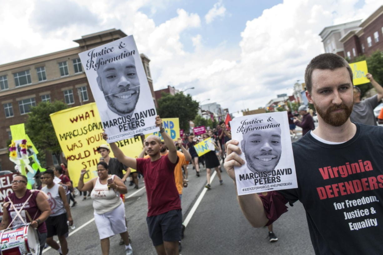 FILE - In this June 2, 2018, file photo, marchers for Marcus-David Peters shout as they head to Richmond Police Headquarters from VCU's Siegel Center in Richmond, Va. Around the U.S., protesters have been calling for prosecutors to take a second look at police killings of Black people, including Peters. Peters was shot May 14 by a Richmond police officer after a confrontation on Interstate 95.