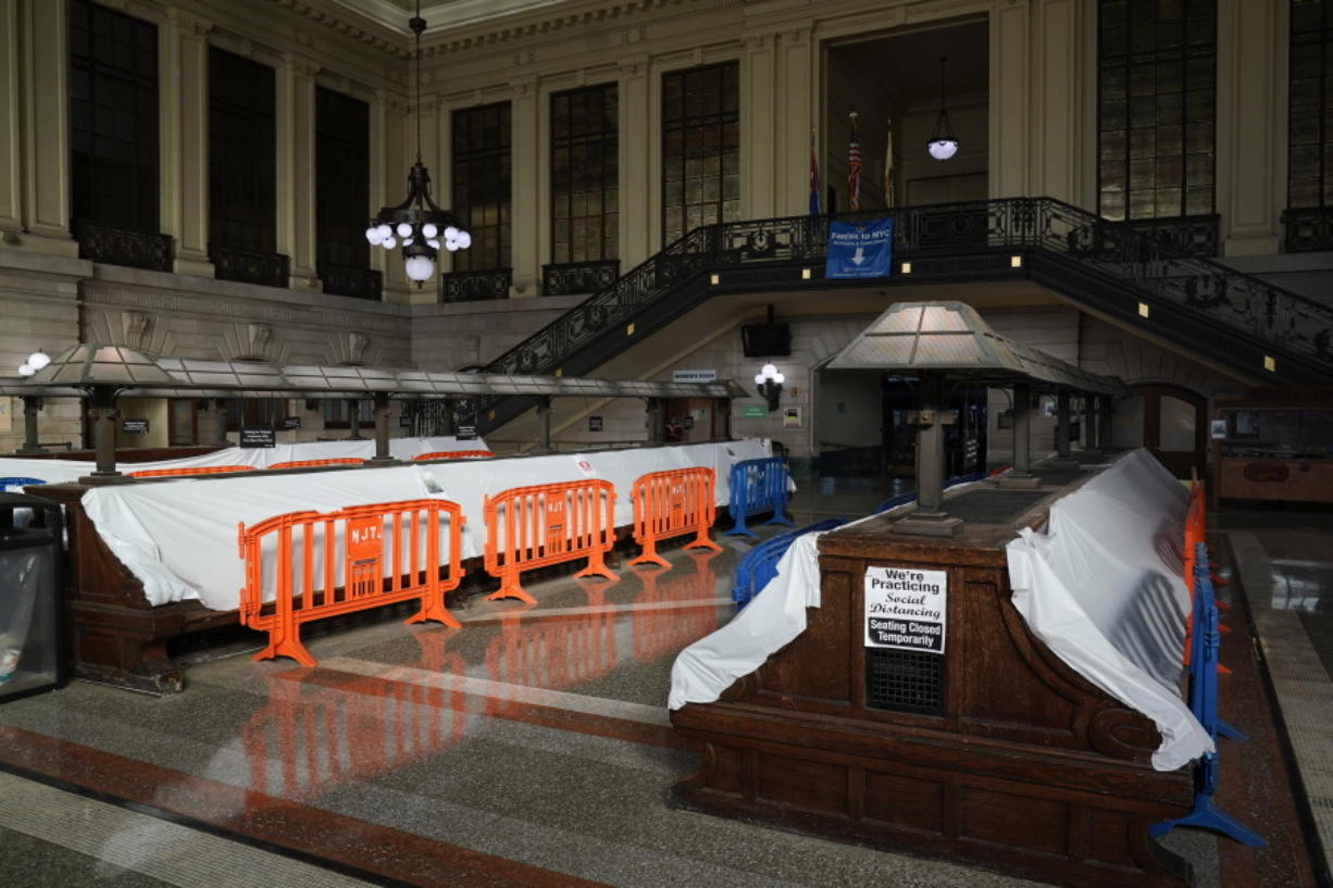 Tarps and fences block the seating area in the Hoboken Terminal waiting room in Hoboken, N.J., Tuesday, Oct. 27, 2020. Once a gleaming symbol of early 20th-century ambition and prosperity, the grand rail terminal now sits as a somber reminder of the daunting challenges facing mass transit in the New York region.