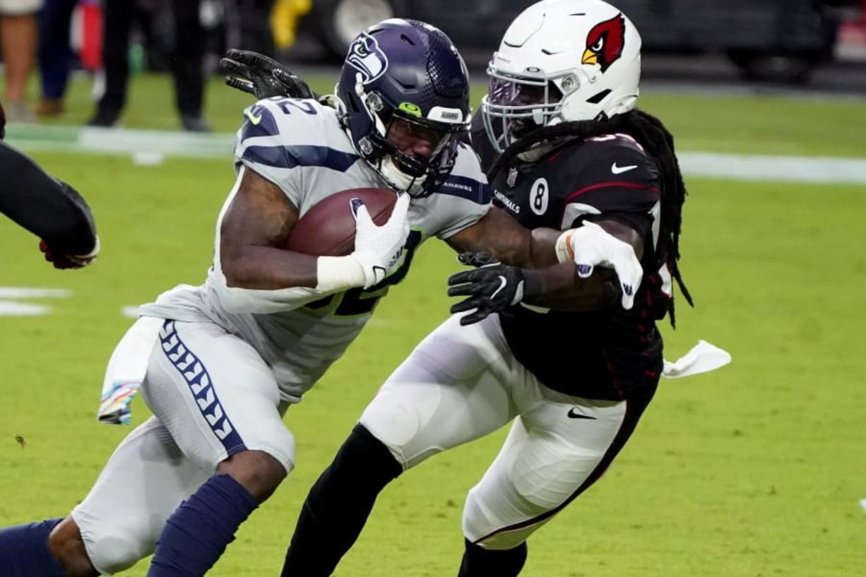 Seattle Seahawks running back Chris Carson (32) runs as Arizona Cardinals outside linebacker De'Vondre Campbell defends during the first half of an NFL football game, Sunday, Oct. 25, 2020, in Glendale, Ariz.