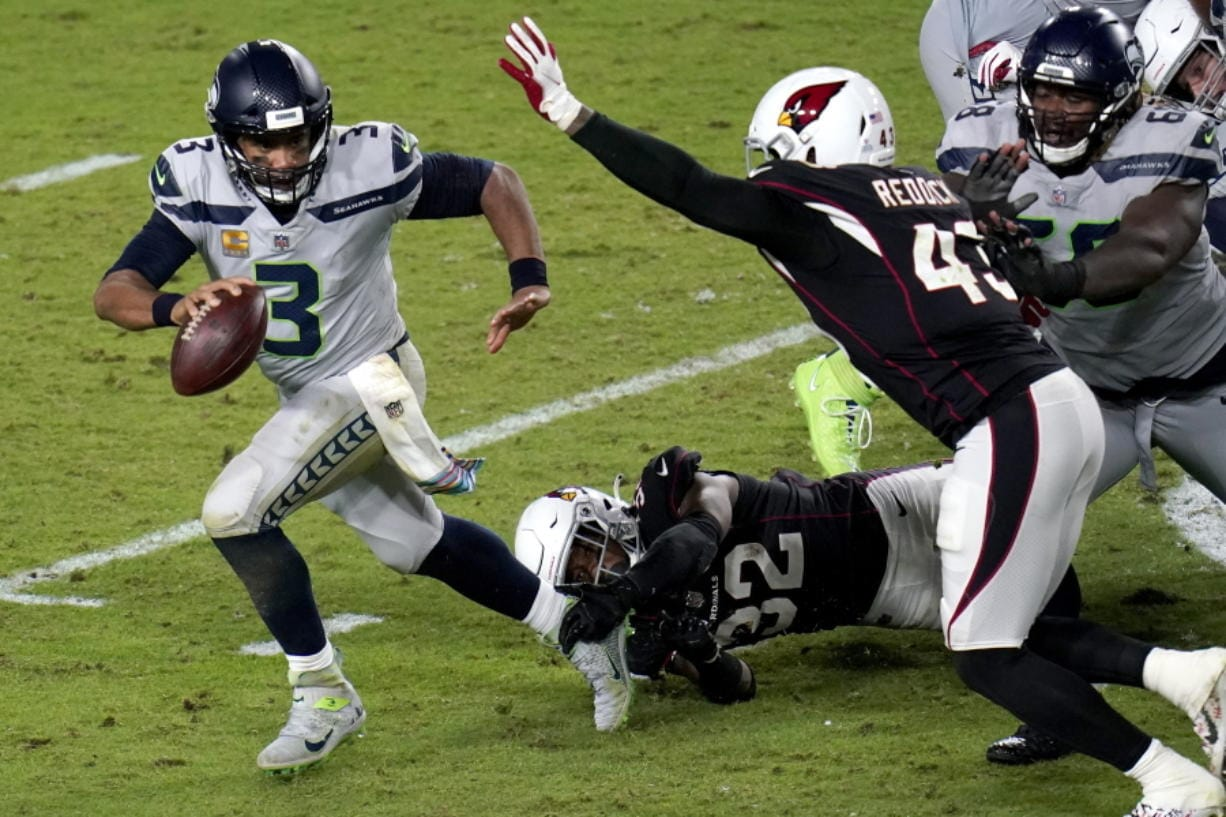 Seattle Seahawks quarterback Russell Wilson (3) escapes the reach of Arizona Cardinals strong safety Budda Baker (32) as outside linebacker Haason Reddick (43) pursues during the second half of an NFL football game, Sunday, Oct. 25, 2020, in Glendale, Ariz. (AP Photo/Ross D.
