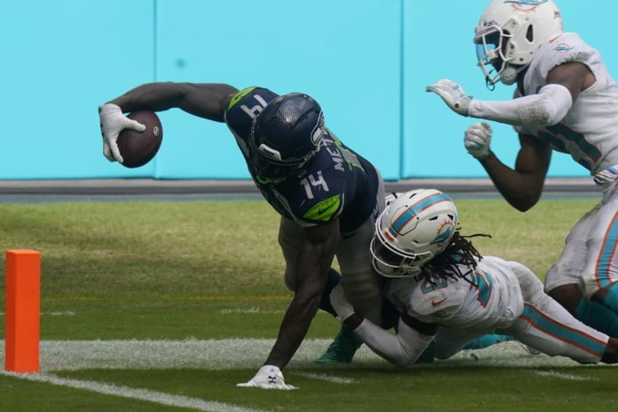 Miami Dolphins strong safety Bobby McCain (28) takes Seattle Seahawks wide receiver DK Metcalf (14) near the end zone, during the second half of an NFL football game, Sunday, Oct. 4, 2020, in Miami Gardens, Fla.