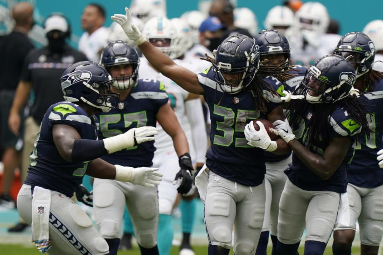 Seattle Seahawks cornerback Ryan Neal (35) is celebrated by his teammates after intercepting a pass, during the first half of an NFL football game against the Miami Dolphins, Sunday, Oct. 4, 2020 in Miami Gardens, Fla.