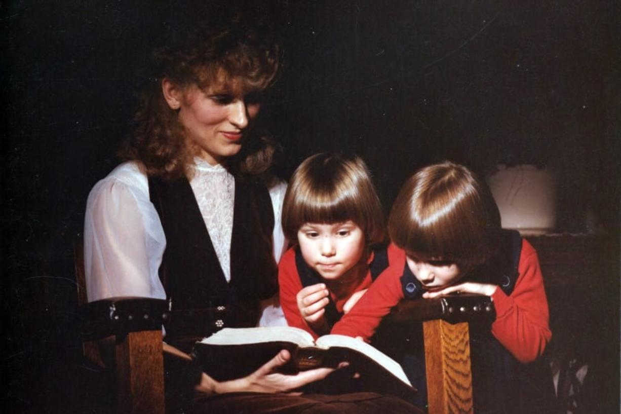 This image provided by Coral Theill, shows Theill with her twin girls in 1984, reading from their family Bible.