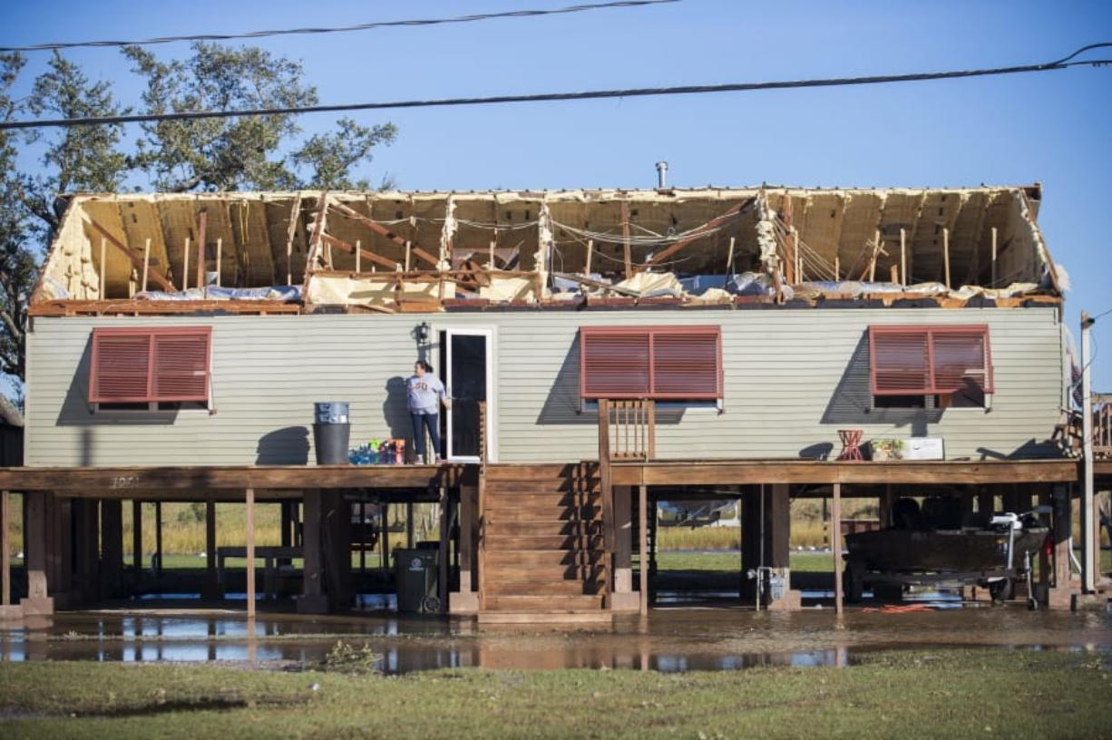 A woman walks out of a house where the roof was torn away during Hurricane Zeta, as people begin the process of cleaning and rebuilding in Chauvin, La., Thursday, Oct. 29, 2020.