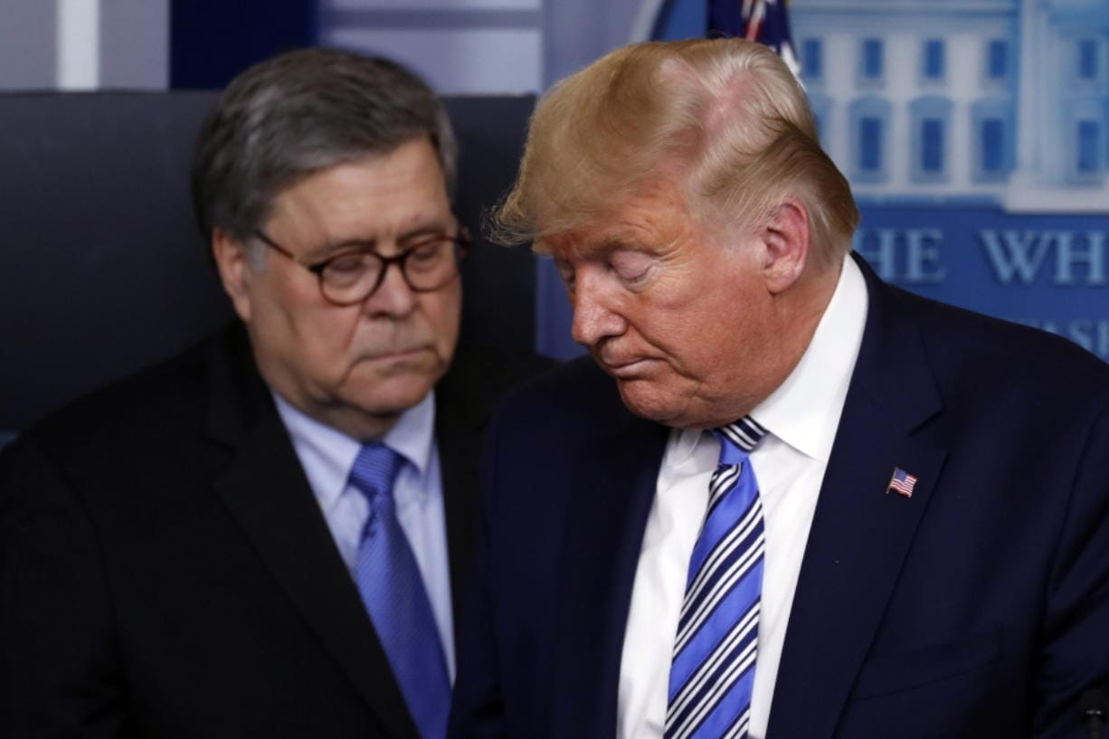 President Donald Trump moves from the podium arch 23 to allow Attorney General William Barr to speak about the coronavirus in the James Brady Briefing Room in Washington.