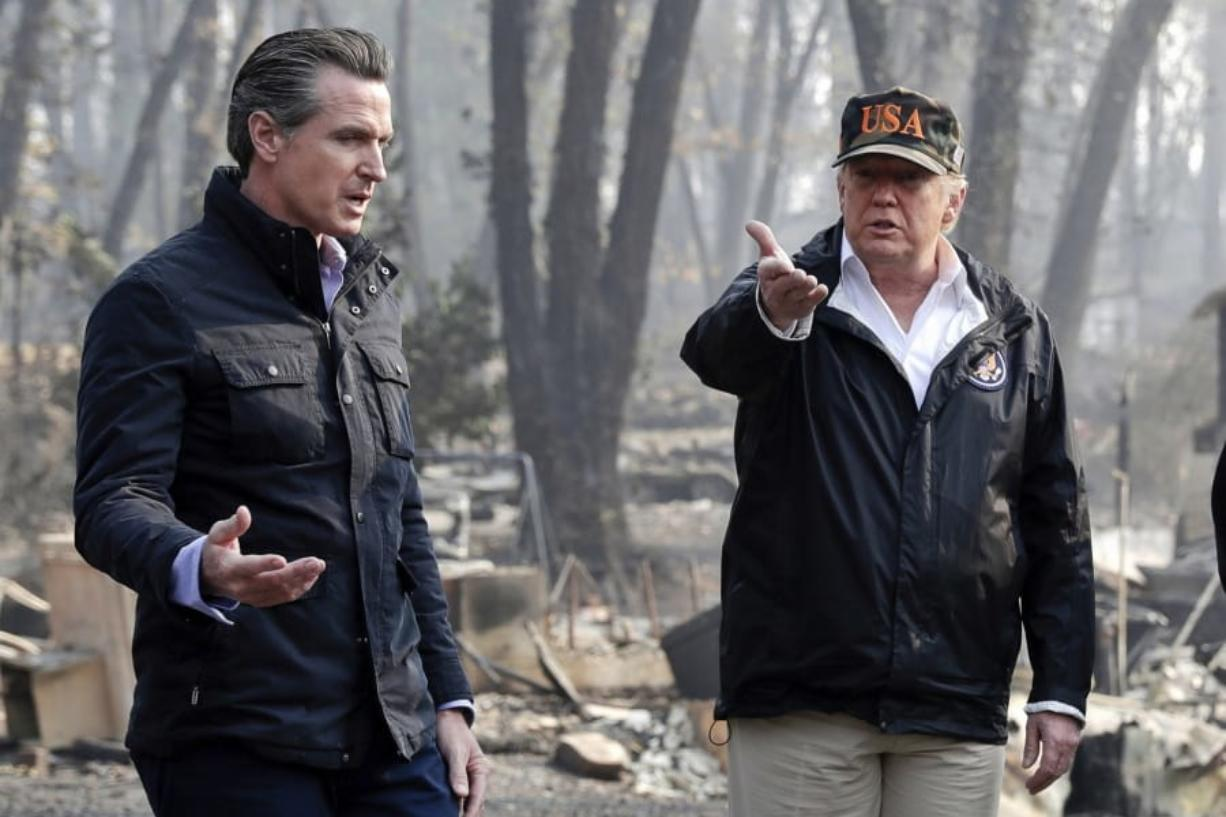 FILE - In this Nov. 17, 2018, file photo, President Donald Trump talks with then California Gov.-elect Gavin Newsom, left, during a visit to a neighborhood impacted by the wildfires in Paradise, Calif. Nearly two years ago President Trump ordered the U.S. Forest Service and the Department of Interior to make federal lands less susceptible to catastrophic wildfires. But the agencies fell short of his goals in 2019, treating a combined 4.3 million acres -- just over half of the 8.45 million acres the president sought. It was only slightly better than their average annual performance over nearly two decades, according to government data.