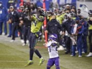 Seattle Seahawks' DK Metcalf (14) pulls in a long pass reception on the Seahawks' last series of an NFL football game as Minnesota Vikings' Cameron Dantzler defends late in the second half, Sunday, Oct. 11, 2020, in Seattle. The Seahawks won 27-26. (AP Photo/Ted S.
