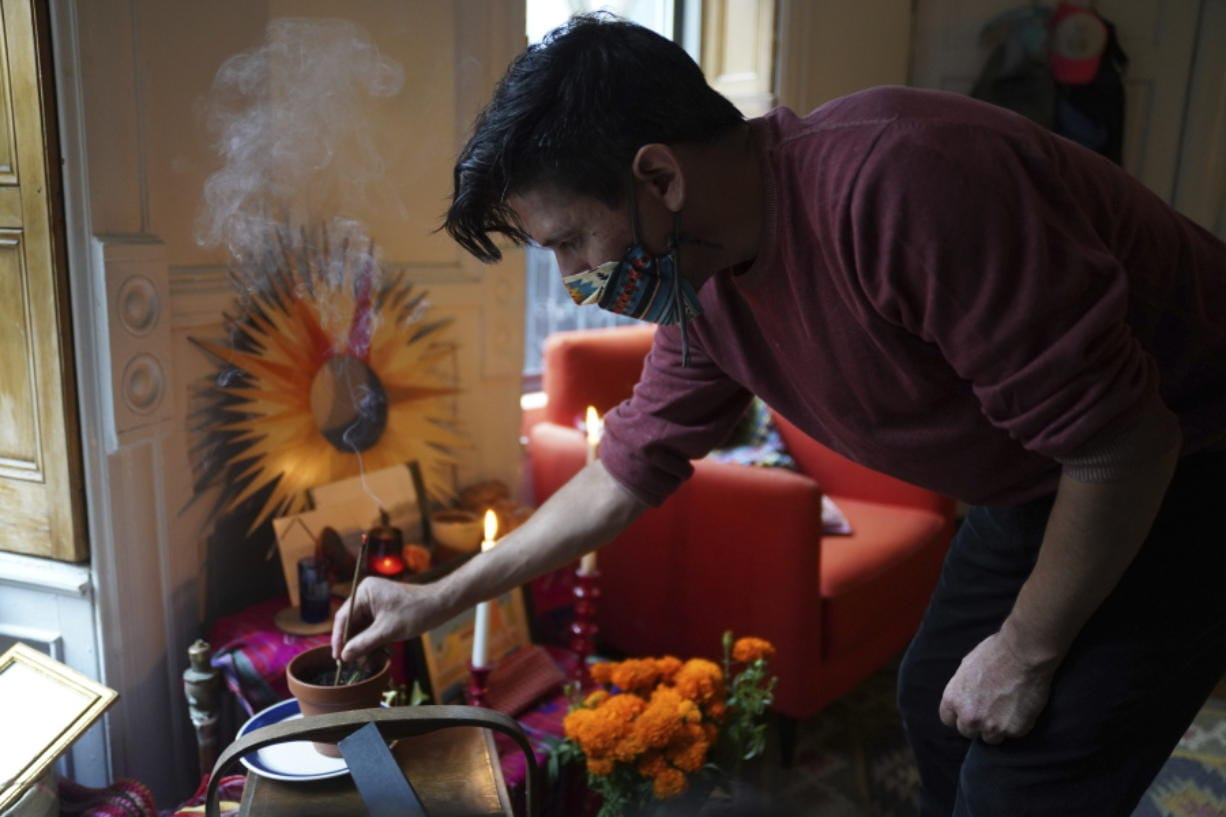 """Sebastian Diaz Aguirre places incense in a Day of the Dead altar dedicated to his father, who died in a nursing home in Mexico last month, Wednesday , Oct. 28, 2020 in the Brooklyn borough of New York """"It feels extremely comforting. I do feel I have a connection with my dad,"""" said Diaz Aguirre, who set up his first ofrenda, or altar, since moving to the U.S. eight years ago."""