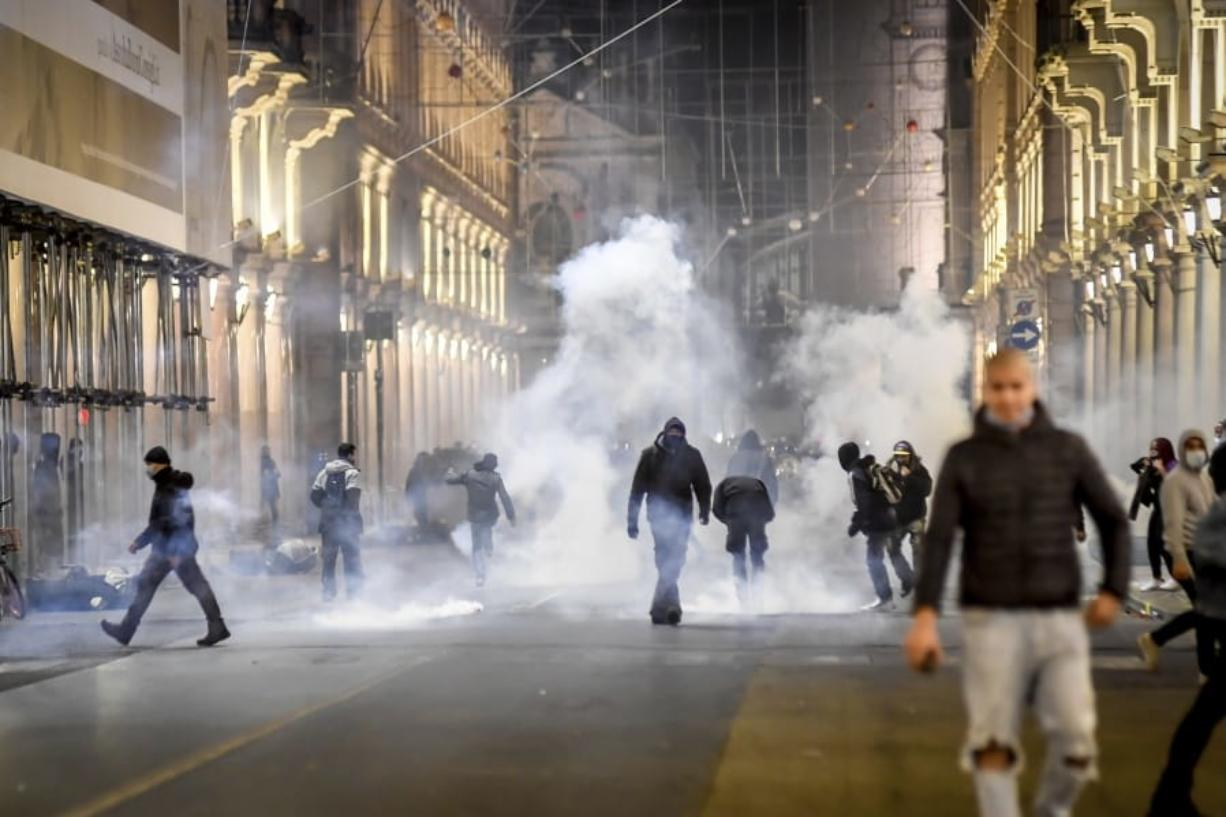 Smoke billows as clashes broke out during a protest against the government restriction measures to curb the spread of COVID-19 in Turin, Italy, Monday, Oct. 26, 2020. Protesters turned out by the hundreds in Italian several cities and towns on Monday to vent anger, sometimes violently, over the latest anti-COVID-19 rules, which force restaurants and cafes to close early, shutter cinema, gyms and other leisure venues. In the northern city of Turin, demonstrators broke off from a peaceful protest and hurled smoke bombs and bottles at police in the city square where the Piedmont regional government is headquartered.