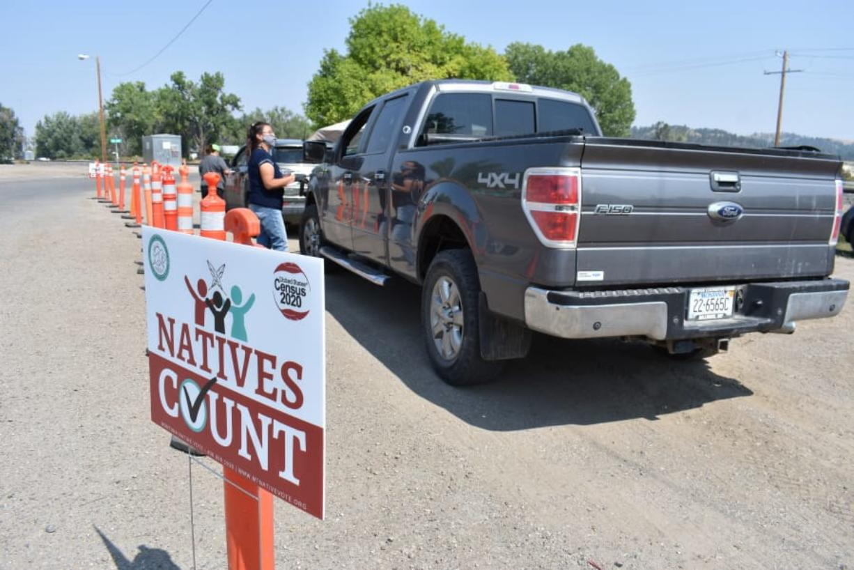 Vehicles stop at a drive-thru U.S. Census participation campaign organized by Montana Native Vote on the Crow Indian Reservation in Lodge Grass, Mont. on Wednesday, Aug. 26, 2020. There have always been geographic and cultural challenges to Census taking on Native lands, but the pandemic dealt a devastating setback.