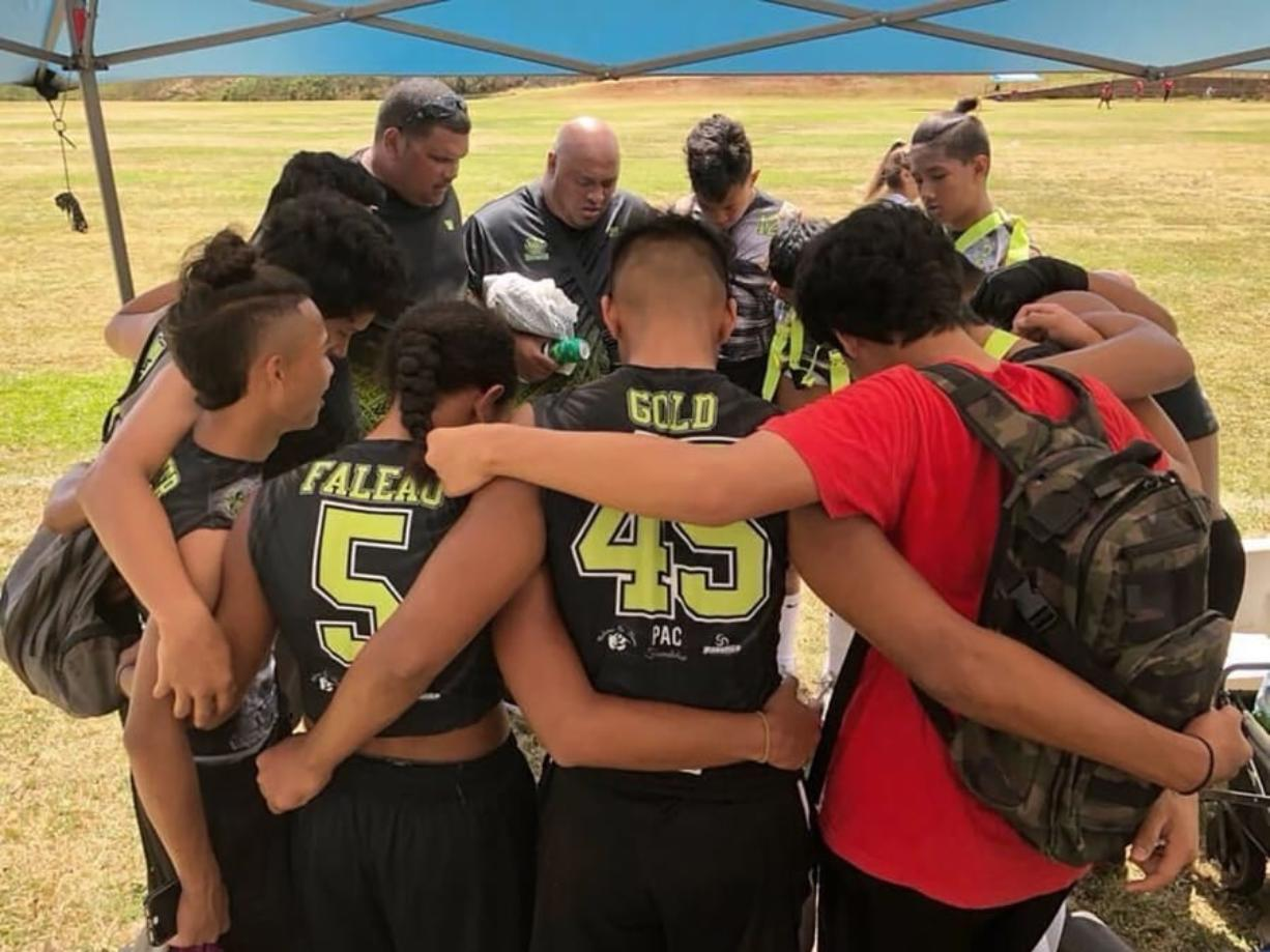 This 2017 photo provided by Ke'ala Aki shows Willie Talamoa, rear center with shaved head, next to Kanohi Aki, rear left, as they pray with players from their 15-and-under flag football team in Honolulu. A Honolulu community is mourning the loss of Talamoa, a mentor, football coach and father figure who died after contracting COVID-19.