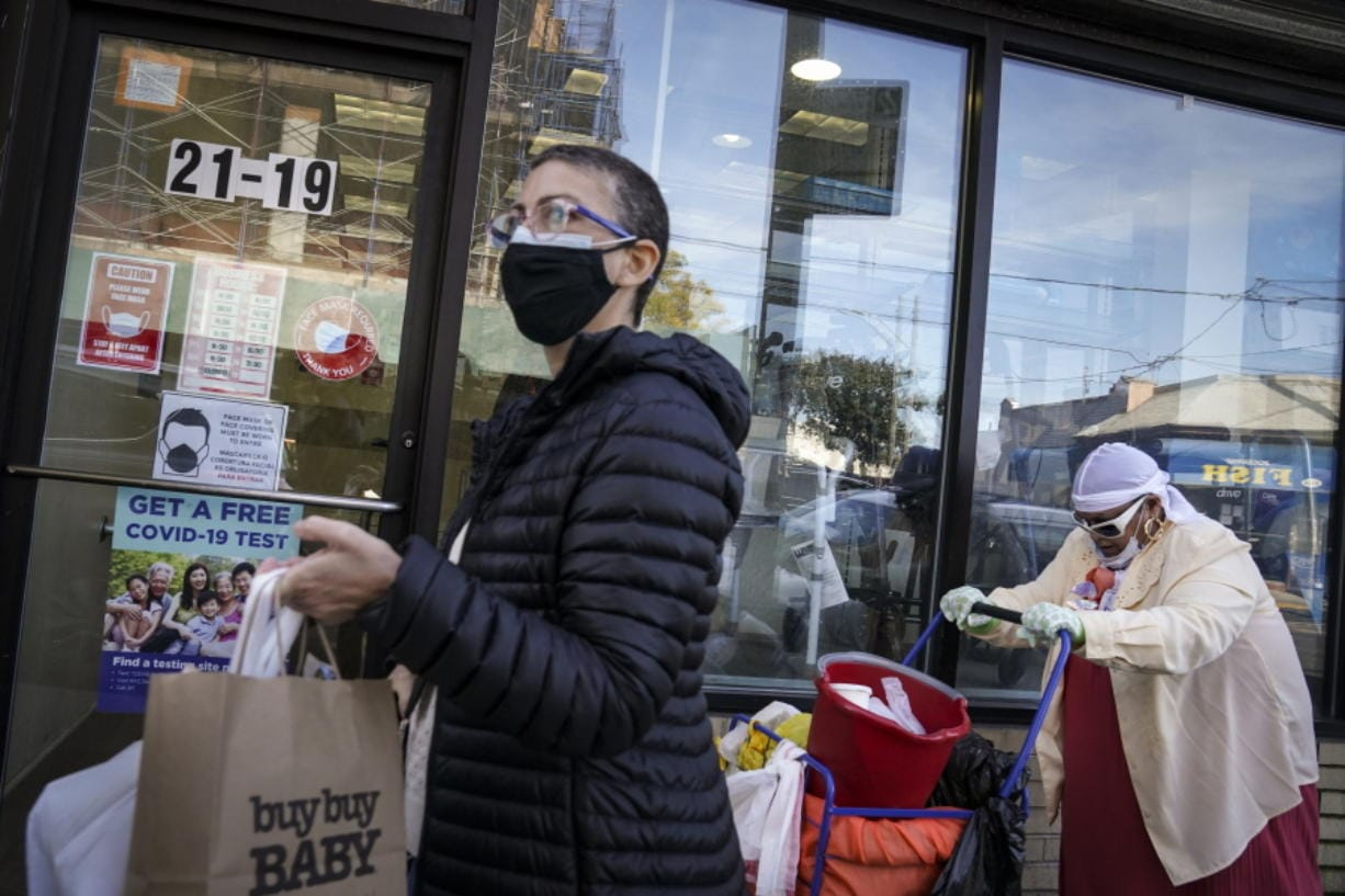 Pedestrians in protective masks pass a storefront on Thursday, Oct. 15, 2020, as restrictions on operations are imposed due to an increase in COVID-19 infections in the Far Rockaway neighborhood of the borough of Queens in New York. After shutdowns swept entire nations during the first surge of the coronavirus earlier this year, some countries and U.S. states are trying more targeted measures as cases rise again around the world. New York's new round of shutdowns zeroes in on individual neighborhoods, closing schools and businesses in hot spots measuring just a few square miles.