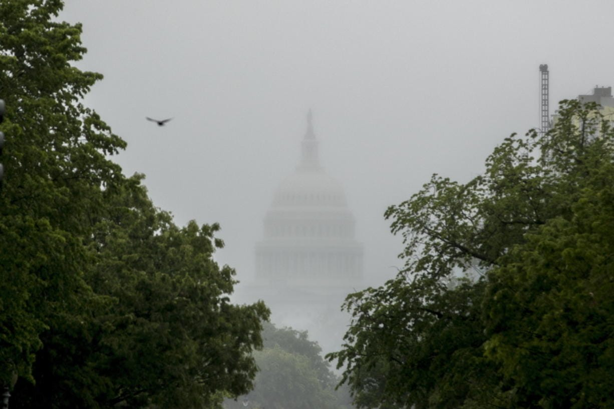 FILE - In this May 22, 2020, file photo the Dome of the U.S. Capitol Building is visible through heavy fog in Washington. New virus relief will have to wait until after the November election. Congress is past the point at which it can deliver more coronavirus aid soon, with differences between House Speaker Nancy Pelosi, Senate Republicans and President Donald Trump proving insurmountable.