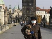 A man wearing a face mask carries his dog across the medieval Charles Bridge in Prague, Czech Republic, Wednesday, Oct. 21, 2020. In another desperate attempt to slow the rise of coronavirus infections in the Czech Republic, Health Minister Roman Prymula has announced a ban on free movement of people in the country and a closure of many stores, shopping malls and hotels. At the same time, state offices will limit their opening hours. Prime Minister Andrej Babis says those measures should prevent the collapse of the health system in early November.