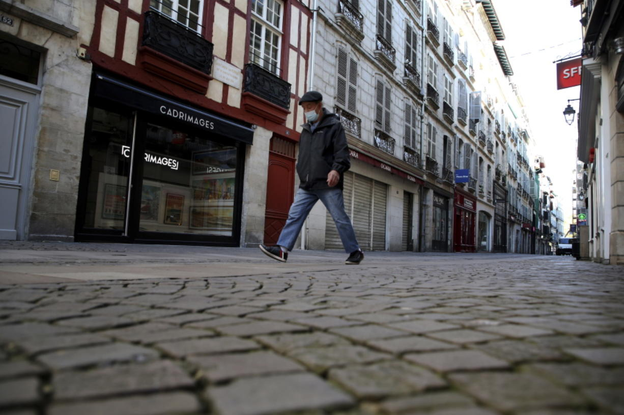 A man walks in an empty street during a nationwide confinement to counter the Covid-19, in Bayonne, southwestern France Friday, Oct. 30, 2020 . France re-imposed a monthlong nationwide lockdown Friday aimed at slowing the spread of the virus, closing all non-essential business and forbidding people from going beyond one kilometer from their homes except to go to school or a few other essential reasons.
