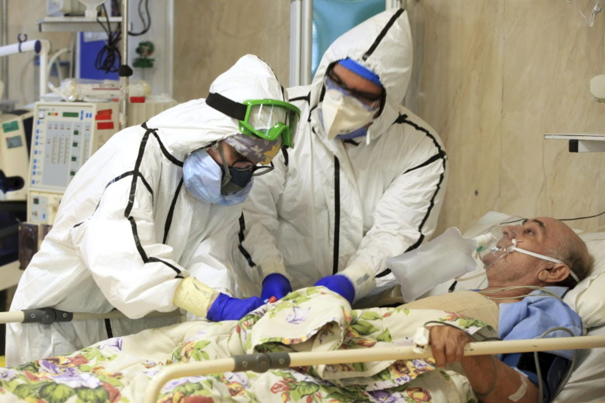 In this Wednesday, Oct. 14, 2020, photo provided by the Iranian Health Ministry, medics tend to a COVID-19 patient at the Shohadaye Tajrish Hospital in Tehran, Iran. Iran is confronting a new surge of infections that is filling hospitals and cemeteries alike.