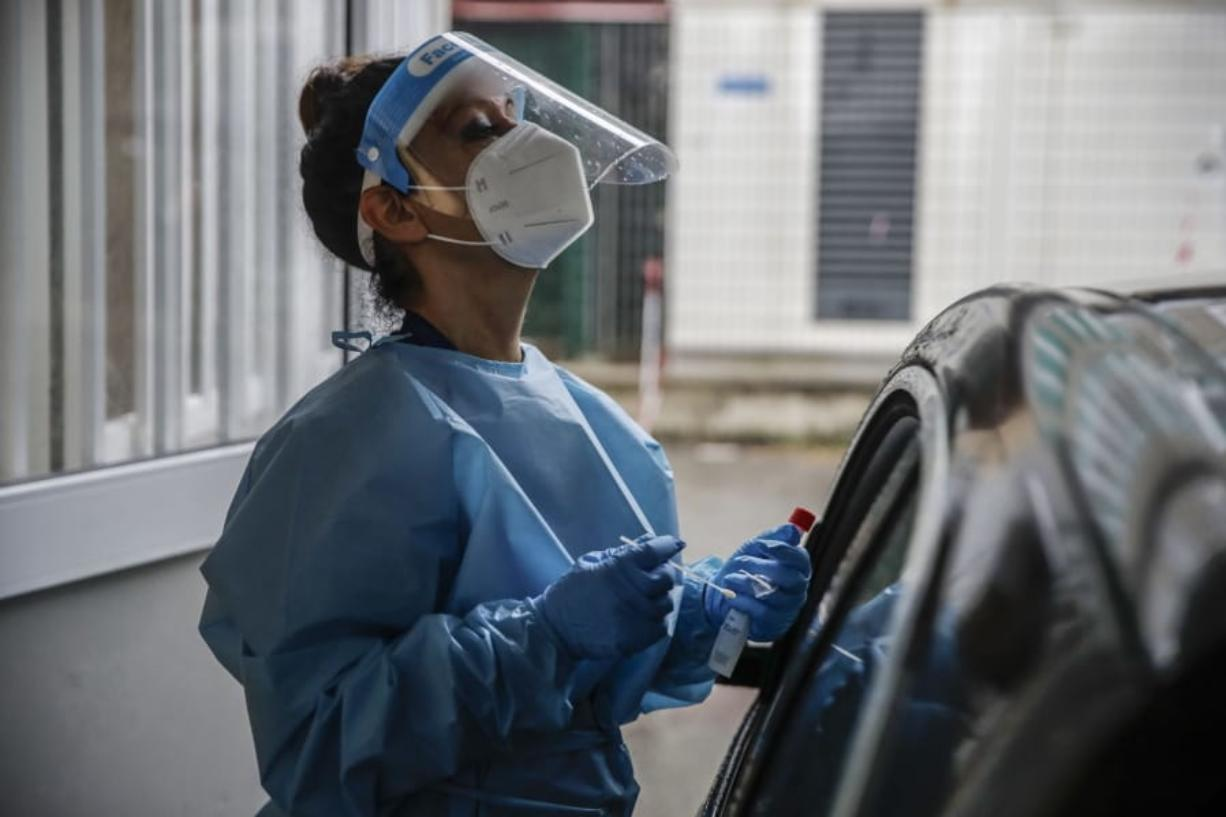 A paramedic takes swabs to test for COVID-19 at a drive-through at the San Paolo hospital, in Milan, Italy, Thursday, Oct. 15, 2020. Coronavirus infections are surging again in the region of northern Italy where the pandemic first took hold in Europe, renewing pressure on hospitals and health care workers.