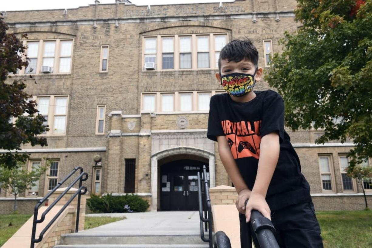 Second grade student Mason Negron, 6, whose mother Kristina Negron was laid off from her job as an aide for a special education class at Schenectady High School, due to budget cuts, poses for a photograph at his Pleasant Valley Elementary school Tuesday, Sept. 29, 2020, in Schenectady, N.Y.