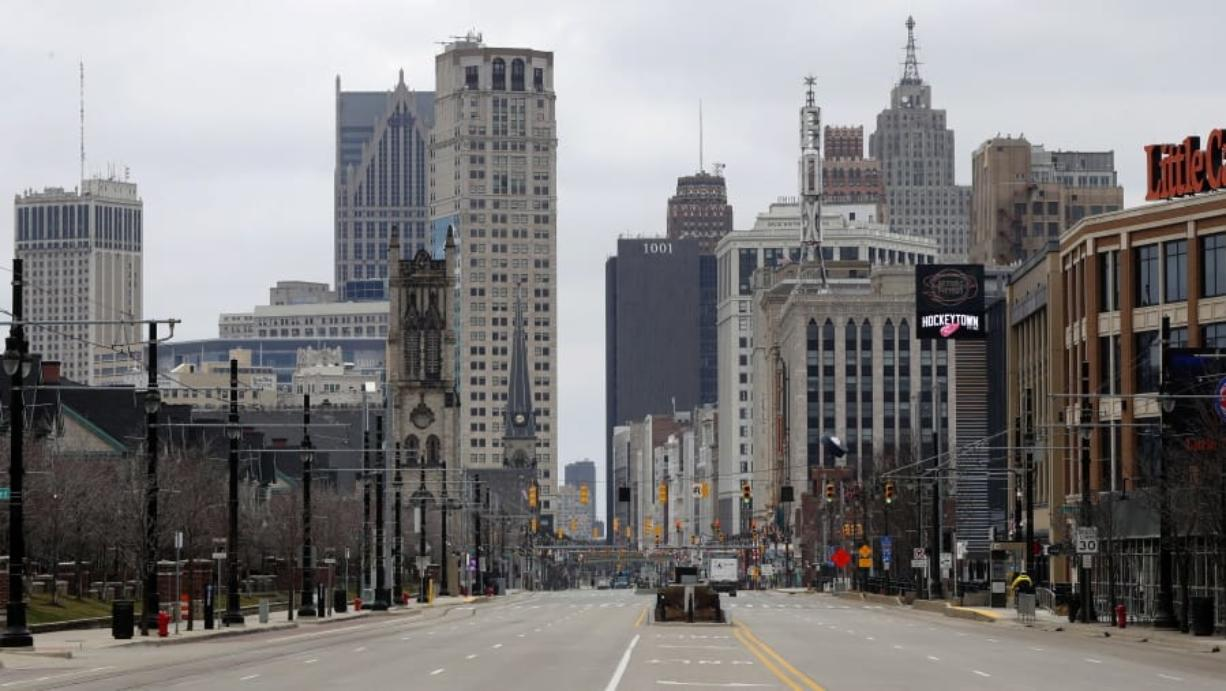 In this March 24, 2020 file photo, Woodward Avenue is shown nearly empty in Detroit. Before the coronavirus showed up, downtown Detroit was returning to its roots as a vibrant city center, motoring away from its past as the model of urban ruin. Now, with the coronavirus forcing many office workers to their homes in the suburbs, those who remain wonder if revitalization will ever return.