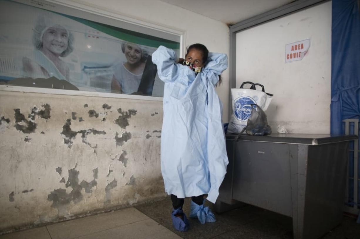 Elena Suazo, a kindergarten cafeteria worker, puts on the protective gear she brought from home, outside the entrance to the COVID-19 wing of Jose Gregorio Hernandez Hospital which used to be the emergency room, as she prepares to enter and care for her 76-year-old hospitalized father, in the Catia neighborhood of Caracas, Venezuela, Thursday, Sept. 24, 2020. In this ruined country, the only way to ensure that he received the care he needed was to do it herself, regardless of the dangers to her own health.