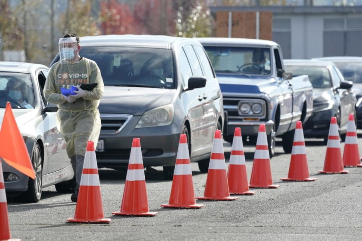 A worker walks along a line of cars Wednesday at a King County COVID-19 testing site in Auburn, south of Seattle. (ted s.
