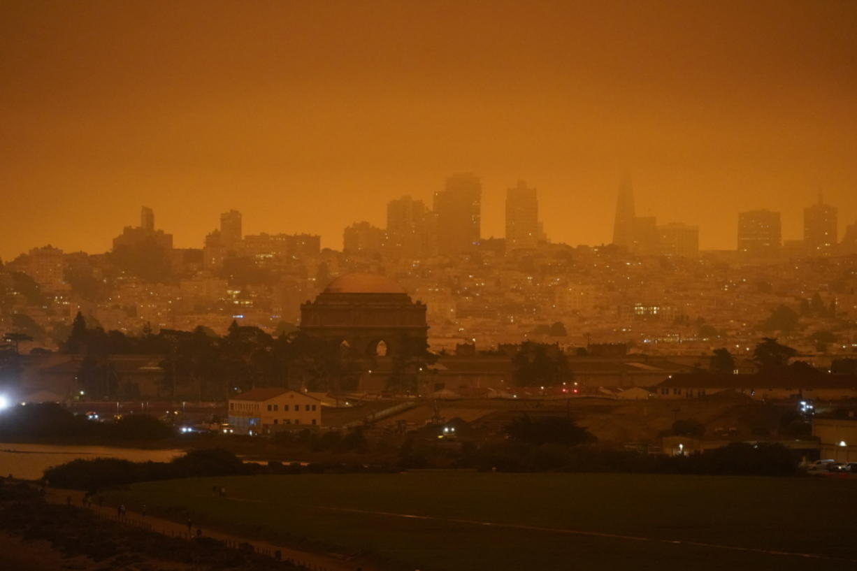 FILE - In this Sept. 9, 2020, file photo, taken at 11:18 a.m., is a dark orange sky above Crissy Field and the city caused by heavy smoke from wildfires in San Francisco. Wildfires that scorched huge swaths of the West Coast churned out massive plumes of choking smoke that blanketed millions of people with hazardous pollution that spiked emergency room visits and that experts say could continue generating health problems for years. An Associated Press analysis of air quality data shows 5.2 million people in five states were hit with hazardous levels of pollution for at least a day.