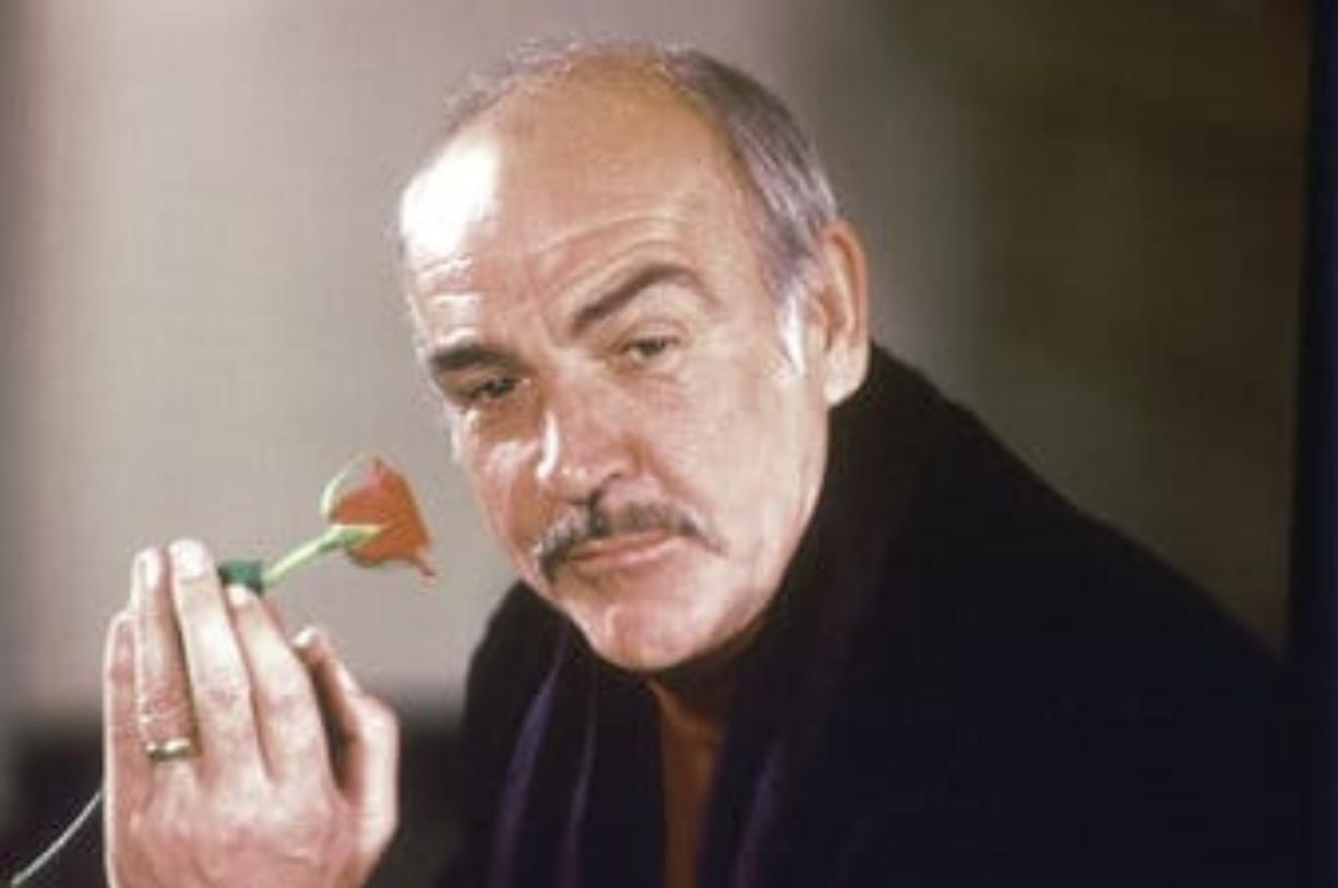 """FILE - In this Jan. 23, 1987 file photo, actor Sean Connery holds a rose in his hand as he talks about his new movie """"The Name of the Rose"""" at a news conference in London.  Scottish actor Sean Connery, considered by many to have been the best James Bond, has died aged 90, according to an announcement from his family."""