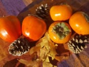 The dark orange, heart-shaped hachiya persimmons, left, require patience and can only be eaten when they're quite squishy. The squat, golden orange fuyu persimmons may be eaten whole like an apple at any stage from crisp to soft.
