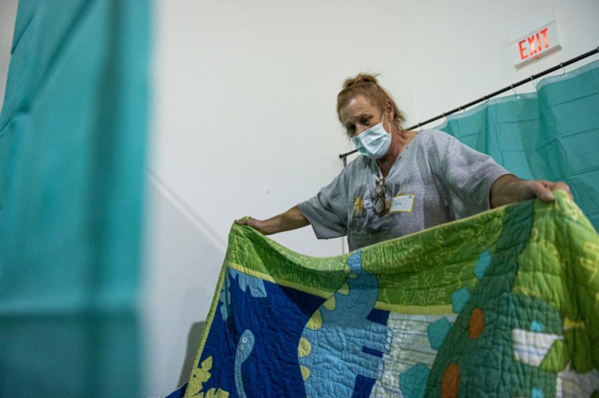 Diana Finn spreads a quilt over her sleeping mat at the Winter Hospitality Overflow shelter at St. Andrew Lutheran Church in Orchards on Monday.