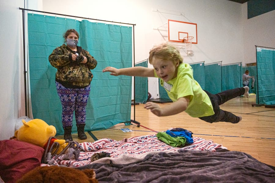 Aaron Morris, 6, leaps onto his mattress while his mother, Merissa Morris, looks on before a night at the Winter Hospitality Overflow shelter at St. Andrew Lutheran Church in Orchards on Monday. (Samuel Wilson/ for the Columbian)
