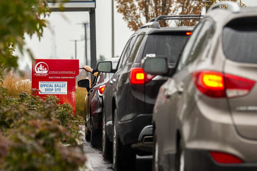 Drivers line up to drop off ballots at a Clark County ballot drop box Tuesday in the Vancouver Mall parking lot. A rush of voters arrived at the box, southeast of Macy's, shortly after noon Tuesday.