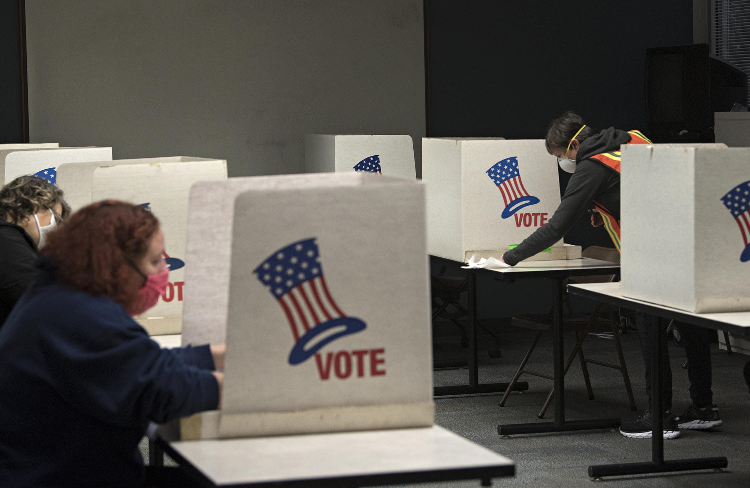 Mary Stender, a temporary worker for the Clark County Elections Office, prepares for the next voter while keeping the democratic process free from coronavirus on Tuesday afternoon, Nov. 3, 2020. (Amanda Cowan/The Columbian)