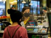 Zaida MacDonald completes a purchase at the New Seasons Market at Fisher's Landing on Tuesday. New Seasons uses plexiglass screens and demands customers wear cloth masks to prevent the spread of the coronavirus, particularly as holiday season approaches.