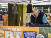 Volunteer Tim Aufmuth processes an Electronic Benefits Transfer card Saturday at the Vancouver Farmers Market's information booth. Customers can redeem their food benefits at the information booth and get a $20 match for fresh fruits and vegetables purchased at the market through the SNAP Market Match program.
