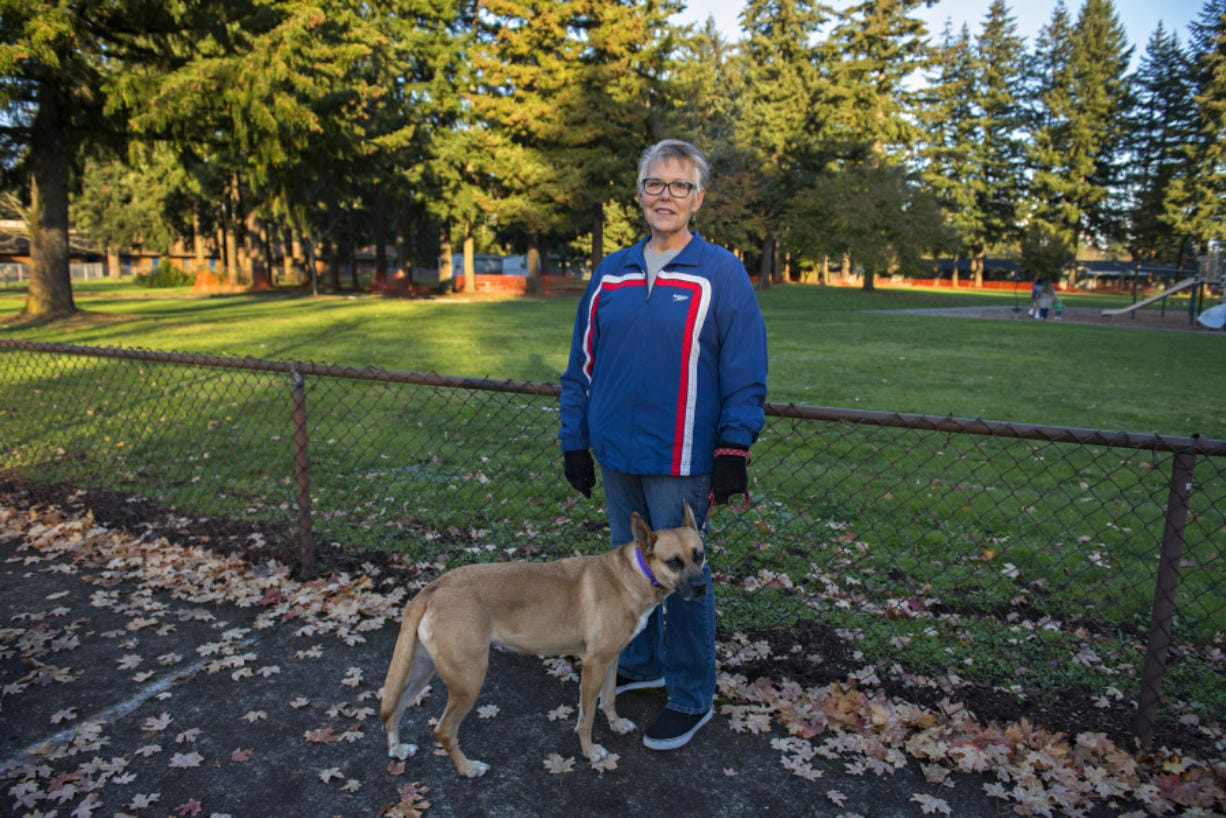 Karen Bean of Vancouver and her dog, DeeDee, pause for a portrait at Hearthwood Park. Bean has volunteered to pull weeds and clean the park.