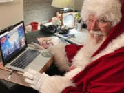 Santa Claus (aka Chuck Gill of Philadelphia) poses for a picture at his desk, where's he's set up for video calls with children and families. Gill uses a platform called Visit With Santa, which originated in Vancouver a few years ago. The COVID-19 pandemic is expected to cause unprecedented demand this year.