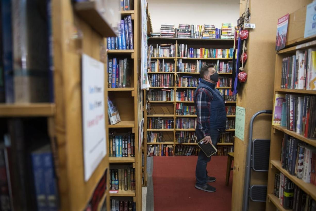 Vancouver resident Tracy Sand wears a protective face mask while browsing through the wide selection at Vintage Books. The store allows a maximum of 10 people in the store at any time.