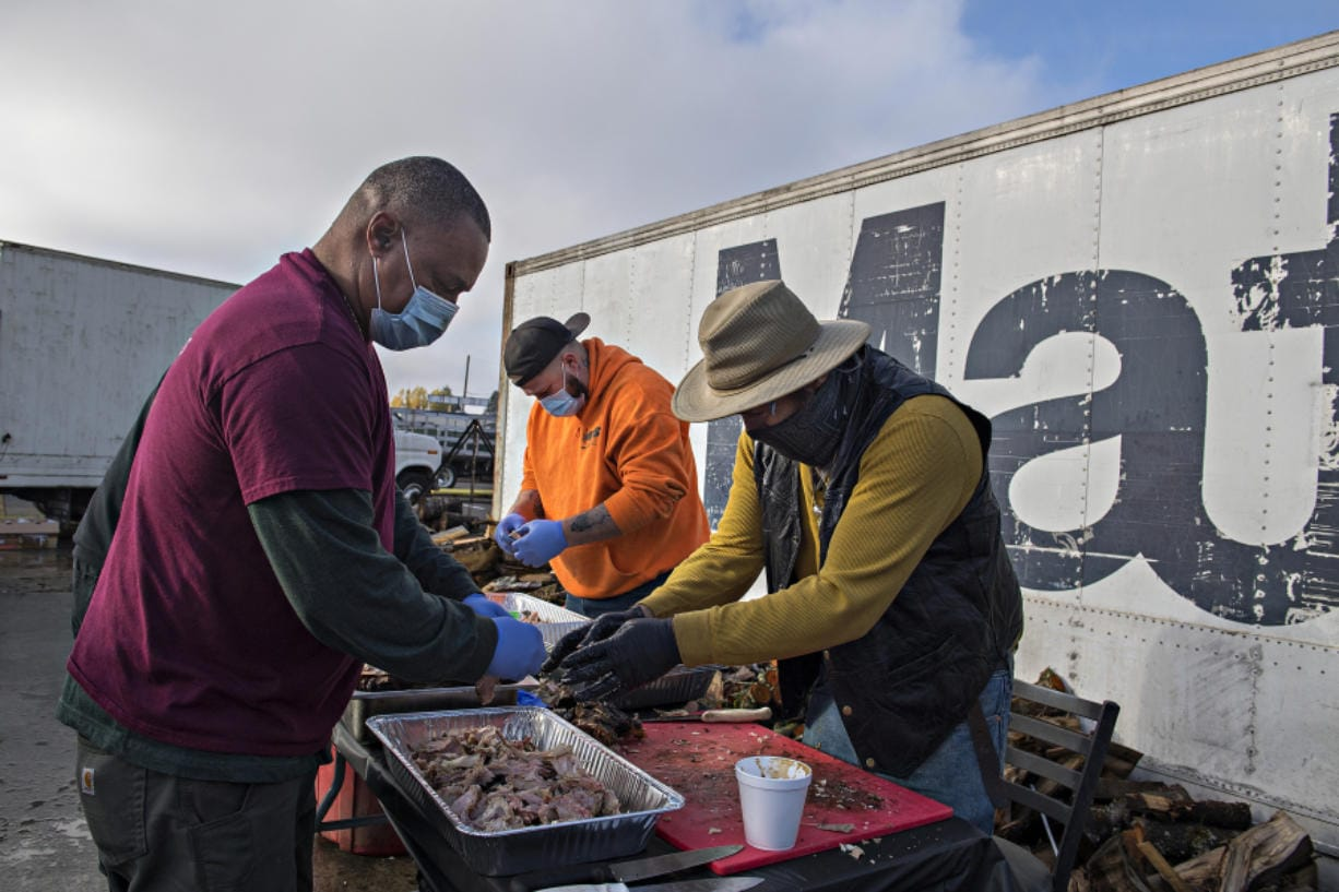 Daddy D's Southern Style BBQ owner Donnie Vercher, left, joins volunteers Chase Alderman and Michael Campbell as they prepare smoked turkey on Friday afternoon. The trio helped make free Thanksgiving meals to feed 3,000 people today.