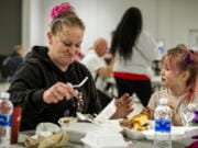 Ashley Green and her daughter, Jordiyn, 7, enjoy a Thanksgiving meal catered by Daddy D's BBQ on Saturday at Living Hope Church. Green has been coming to Living Hope for eight years, and the church provided services that helped Green get out of homelessness.
